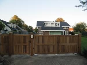 Dichte houten poort met ondergrondse poortopener en intercomsysteem.