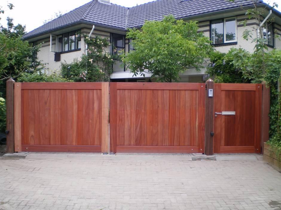 Dicht grote houten hek met loop hek er naast en voorzien van hekautomatisering. Hek - Dicht, hardhouten inrijhek (rood) met looppoort en ondergrondse hekopener - Farm Poorten.