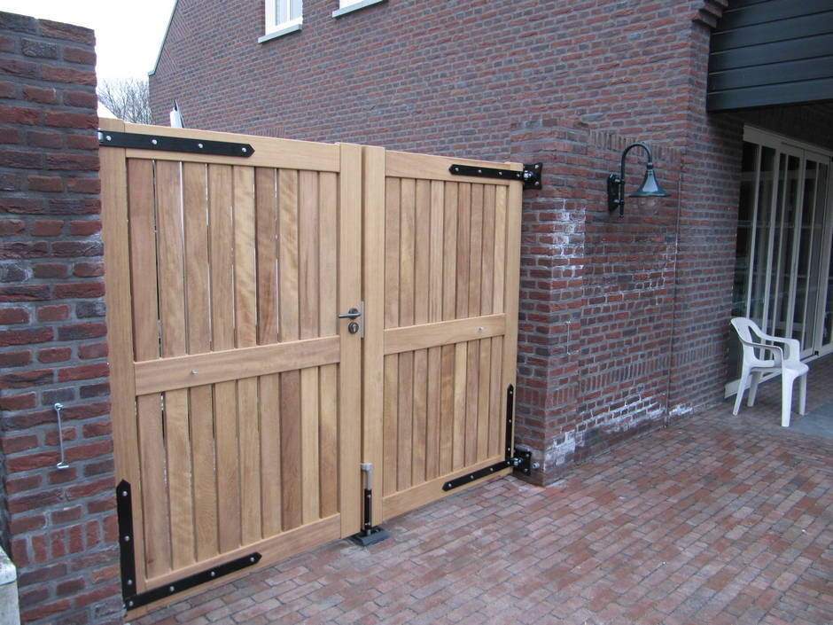 Strak houten hek van zeer duurzaam Iroko hout met smeedijzeren beslag.