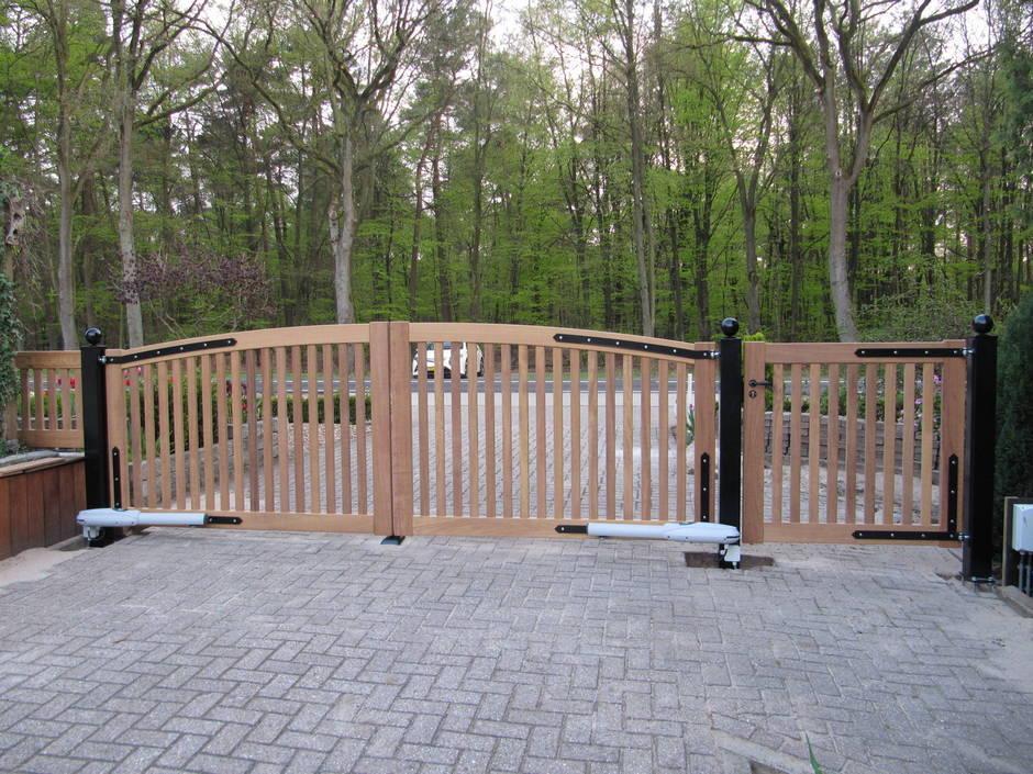 Groot houten hek met hekwerk in zelfde stijl. Op maat gemaakt van zeer duurzaam hout. Houten hekwerk met open inrijpoort voorzien van lineaire poortopener - Farm Poorten.