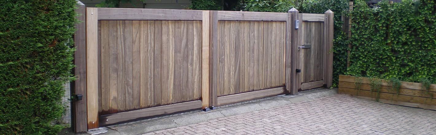 Dichte houten poort met poortautomatisering en intercomsysteem. Zeer duurzaam hout.