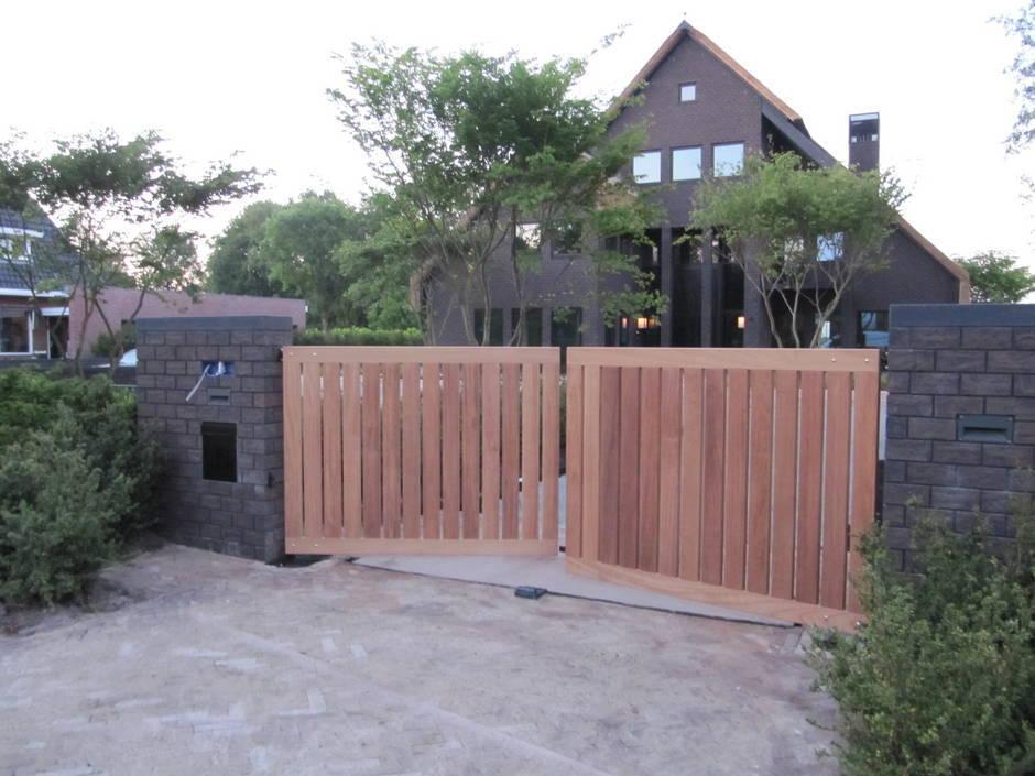 Strakke houten elektrische inrijpoort. Op maat gemaakt van zeer duurzaam hout en voorzien van smeedijzeren beslag. Houten dichte inrijpoort met ondergrondse poortopener - Farm Poorten.