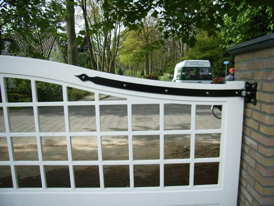 Maatwerk witte houten poort. Half open. Voorzien van maatwerk massief smeedijzeren beslag.