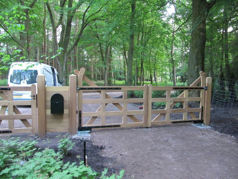 Engelse houten poort, landelijke stijl. Automatische poort voorzien van ondergrondse poortopener. Met op maat gemaakt smeedijzeren beslag. Inrijpoort, looppoort en brievenbus deel.
