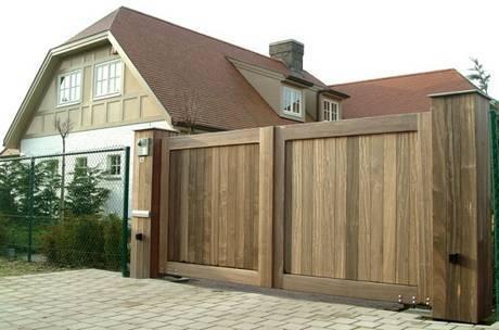 Gesloten of dichte houten poort. Strakke vormgeving. Voorzien van poortautomatisering voor automatisch openen en sluiten en voorzien van videofoonsysteem.