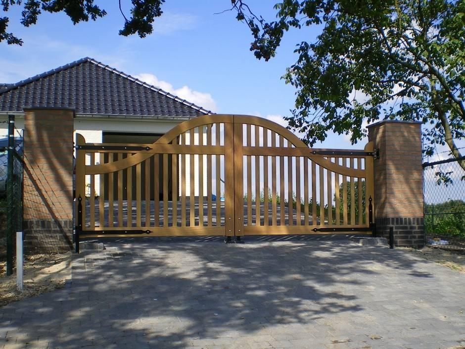 Inrijpoort van hout. Landelijk open model. Voorzien van smeedijzeren beslag. Inrijpoort - Houten poort - Open hardhouten inrijpoort met ondergrondse poortopener - Farm Poorten.