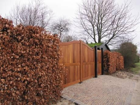 Grote dichte houten poort. Zeer duurzaam met ondergrondse poortopener. Poort met looppoort er naast