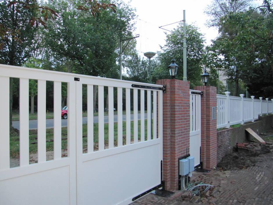 Dubbele poort van zeer duurzaam hout en voorzien van topkwaliteit laklaag wit. Toegangspoort, looppoort en hekwerk. Smeedijzeren beslag en poortautomatisering.