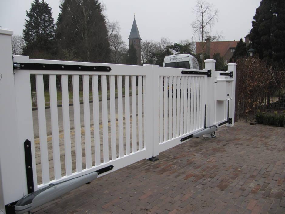 Witte dubbele automatische poort. Toegangspoort met looppoort van zeer duurzaam hout. Voorzien van witte topkwaliteit laklaag en geintegreerde brievenbus. De poort gaat elektrisch open door bovengrondse lineaire poortopeners.