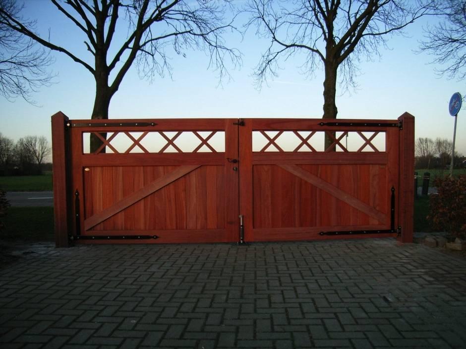 Zeer duurzame houten inrijpoort, dichte houten poort voorzien van smeedijzeren beslag. Poort vergrijsd.