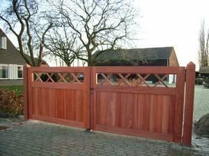 Houten inrijpoort, dichte houten poort voorzien van smeedijzeren beslag.