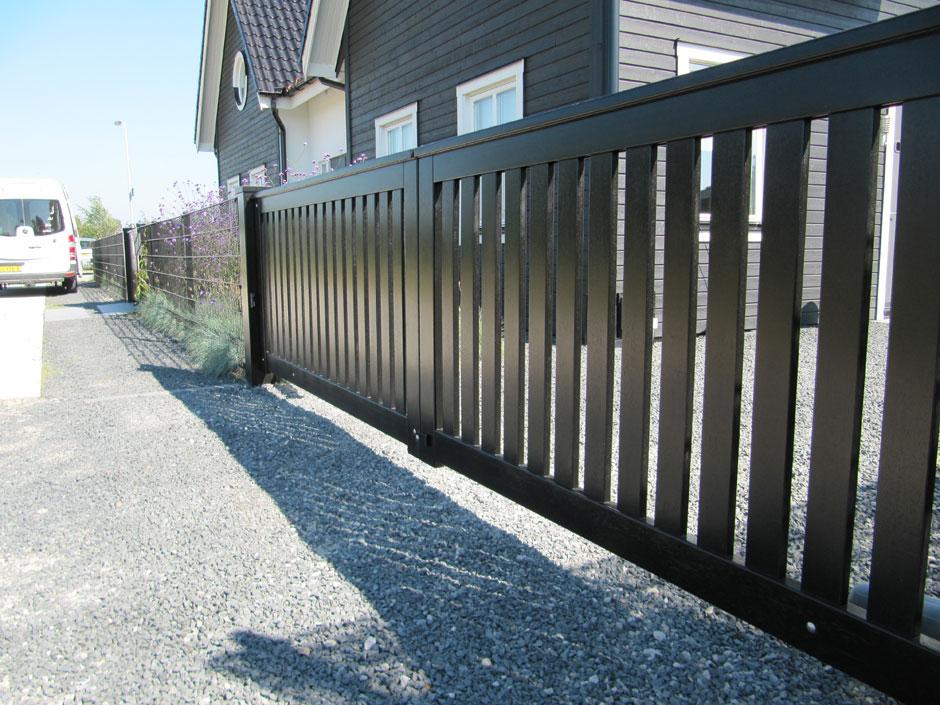 Automatische poort van hout. Strakke vormgeving. Deze poort is geautomatiseerd middels lineaire poortopeners.